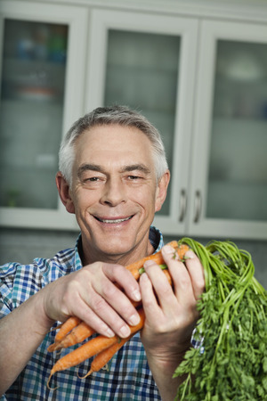 Germany,Berlin,Senior Man Holding Carrots,Portrait LANG_EVOIMAGES