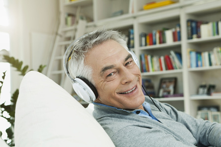 Germany,Berlin,Senior Man With Head Phones On Couch,Portrait