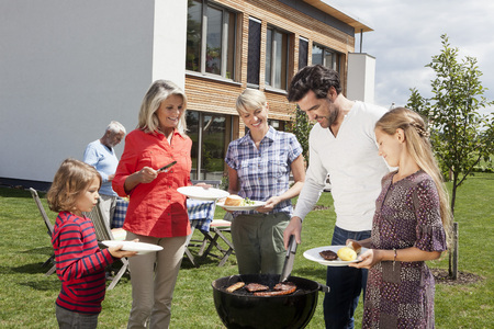 Germany,Bavaria,Nuremberg,Family Standing Around Barbecue In Garden LANG_EVOIMAGES