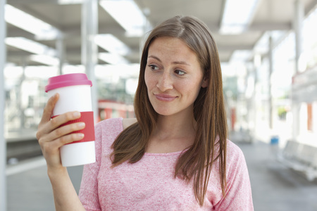 Germany,North-Rhine-Westphalia,Duesseldorf,Young Woman Holding Coffee Cup LANG_EVOIMAGES