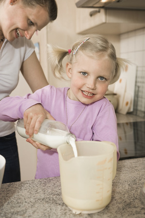 Mother And Daughter Pouring Milk Into Measuring Cup
