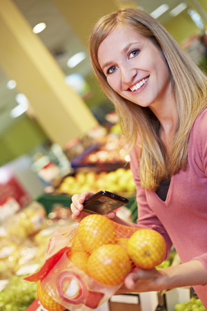 Germany,Cologne,Young Woman With Smart Phone And Oranges In Supermarket,Smiling