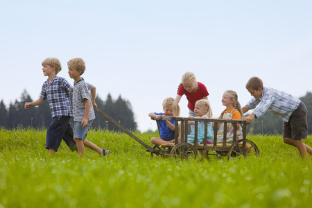 Germany,Bavaria,Group Of Children Playing With Hand Cart