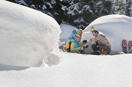 cowering: Austria,Salzburg County,Family Sitting Near Igloo