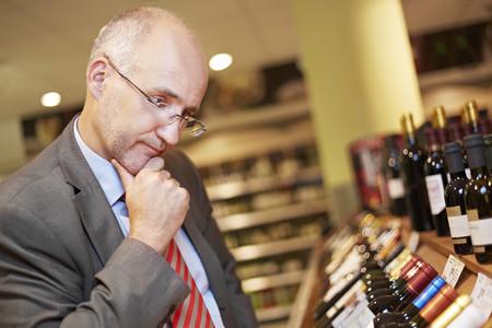 Germany,Cologne,Mature Man Inspecting Wine In Supermarket LANG_EVOIMAGES