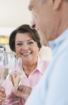 Germany,Leipzig,Senior Man And Woman Drinking Sparkling Wine,Smiling LANG_EVOIMAGES