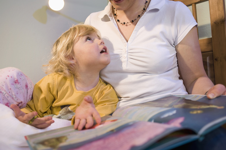 bedtime story: Mother Teaching Daughter In Bedroom LANG_EVOIMAGES