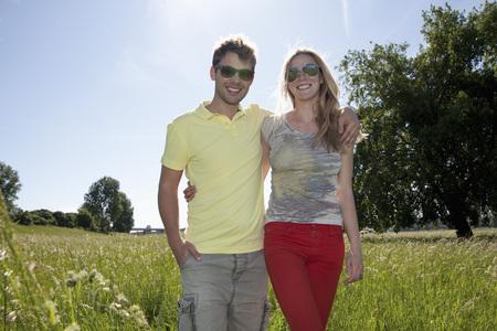 Germany,North Rhine Westphalia,Duesseldorf,Couple Walking In Grass,Smiling