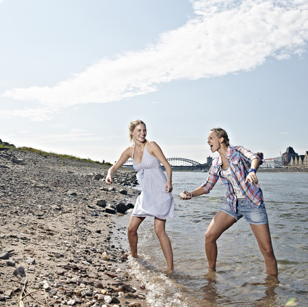 Germany,Cologne,Young Women Skipping Stones In River
