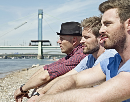 Germany,Cologne,Young Men Sitting On Riverbank