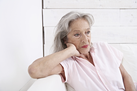 Spain,Mallorca,Sad Senior Woman Sitting On Couch