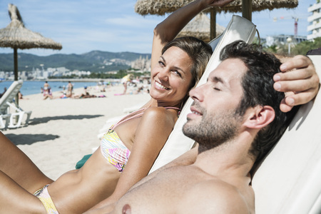 nackte brust: Spain,Mid Adult Couple Relaxing On Beach Chair LANG_EVOIMAGES