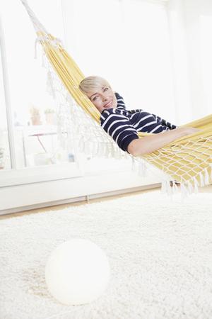 indoor shot: Germany,Bavaria,Munich,Woman Relaxing In Hammock,Portrait
