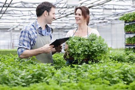 Germany,Bavaria,Munich,Mature Man And Woman With Clip Board In Greenhouse LANG_EVOIMAGES