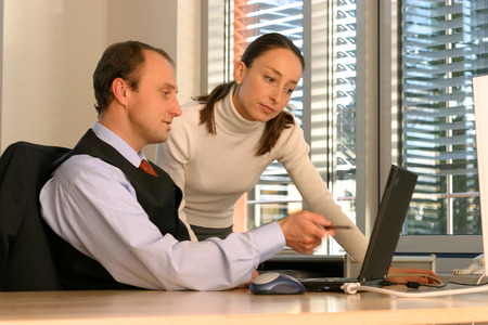 technolgy: Man And Woman In Office, Working On Laptop