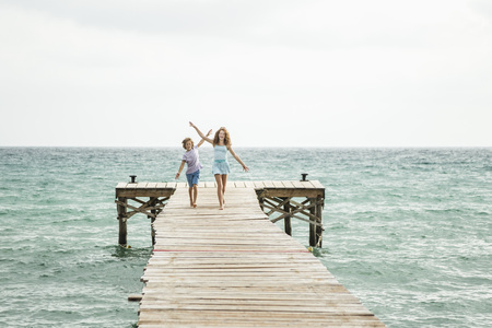 Spain,Girl And Boy Running On Jetty At The Sea