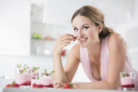 Germany,Young Woman Holding Strawberry,Smiling LANG_EVOIMAGES