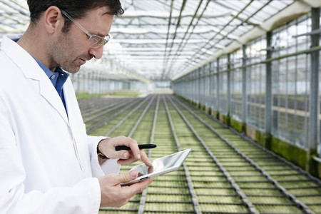 Germany,Bavaria,Munich,Scientist In Greenhouse With Digital Tablet Examining Bed With Seedlings