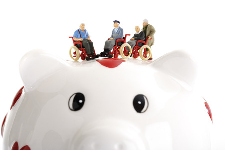 Figurines In Wheelchairs On Piggy Bank
