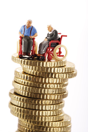 Figurines In Whellchair On Pile Of Coins LANG_EVOIMAGES