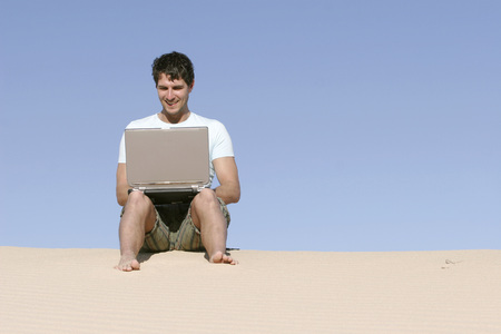 Man Sitting On A Dune With Laptop LANG_EVOIMAGES
