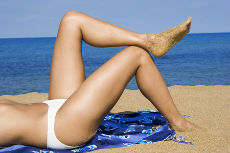 Woman Relaxing On Beach, Side View, Low Section