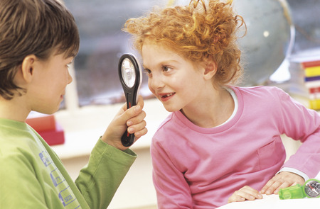 enquiring: Boy And Girl (6-9) Looking At Eachother With Magnifying Glass