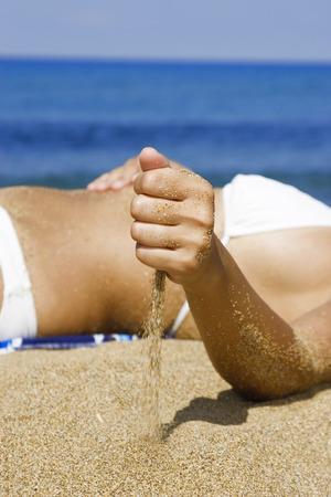 Woman In Bikini Lying On Beach, Mid-Section