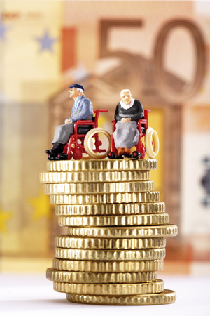 Figurines In Wheelchairs On Pile Of Coins