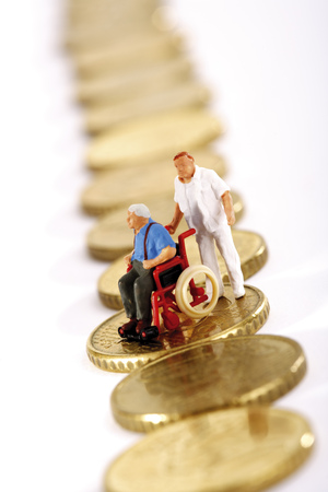 Figurine In Wheelchair And Caregiver On Row Of Coins LANG_EVOIMAGES