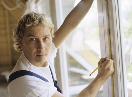 Man Measuring Window Frame