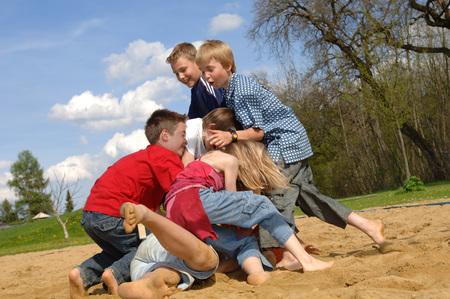 Children Tussling On Playground