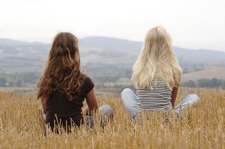 Two Girls Sitting In A Corn Field