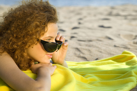 Young Woman Wearing Sunglasses,Relaxing On Beach,Side View