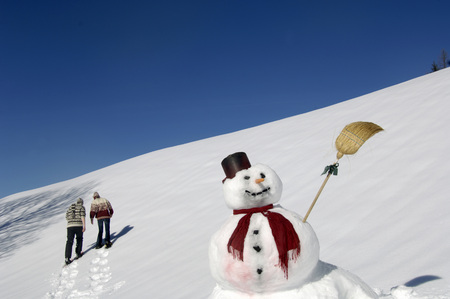 Snow Man, Couple Walking In Background