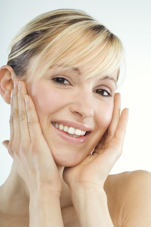 Young Woman Smiling, Hands On Face LANG_EVOIMAGES