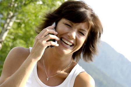 Woman Using Mobile Phone,Laughing,Close-Up LANG_EVOIMAGES