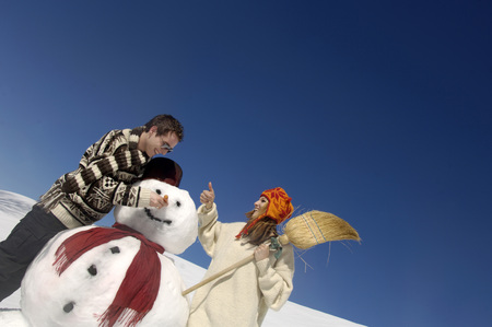 Young Couple With Snow Man