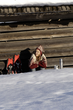 Woman Relaxing In Front Of Alpine Hut