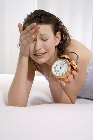 Young Woman Lying On Bed With Alarm Clock, Close-Up LANG_EVOIMAGES