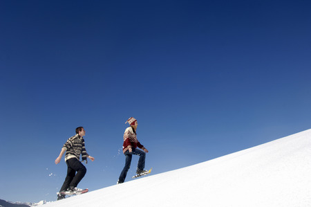 Young Couple In Snow, Walking Uphill