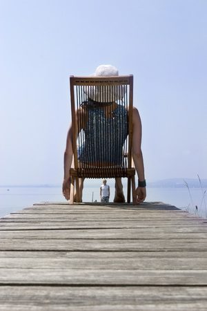 Young Woman Sitting On Deck Chair On Jetty, Rear View LANG_EVOIMAGES