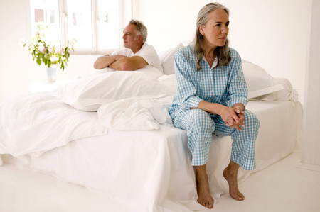 Mature Couple Sitting On Bed (Focus On Woman In Foreground) LANG_EVOIMAGES