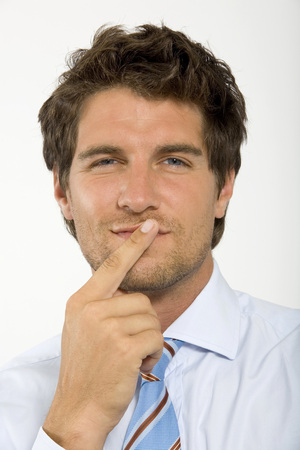 Young Businessman With Finger On Lips,Smiling,Close-Up,Portrait