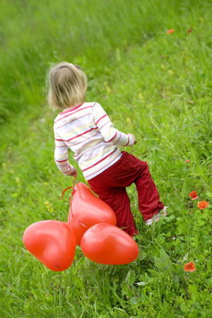hearted: Girl ( 3-4 ) Holding Bunch Of Balloons, Walking In Meadow, Rear View LANG_EVOIMAGES