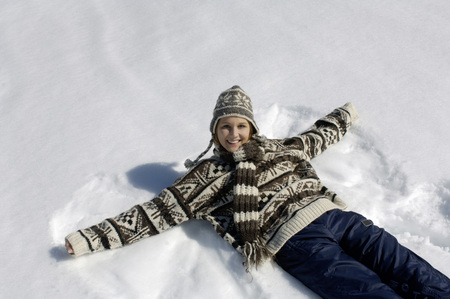 Young Woman Lying On Snow, Smiling, Portrait