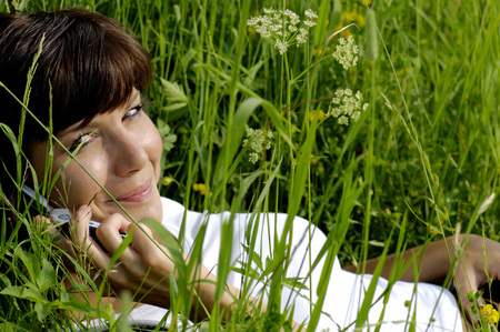 Woman Lying In Field Using Mobile Phone,Elevated View