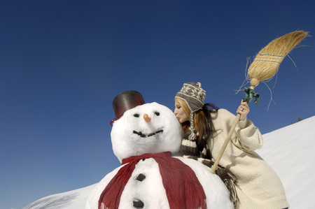 Young Woman Kissing Snowman, Low Angle View