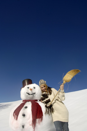Young Woman Leaning On Snowman, Holding Broom, Low Angle View