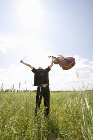 Young Man Standing In Field With Cello,Arms Out
